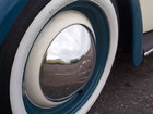 Vans reflected in a Beetle's wheel